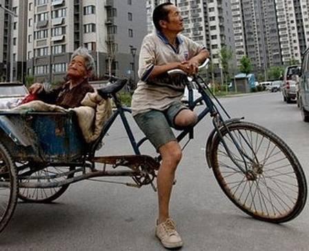 Com a mãe inválida na garupa, o chinês recolhe lixo reciclável e consegue R$ 60 por mês