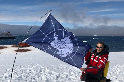 Brad with Antarctic flag. The ship and icebergs are visible in the sea.  Penguins and research hut also visible.