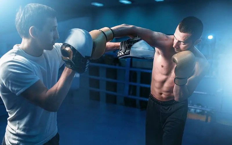 Boxer in gloves exercises with personal trainer mitt drills