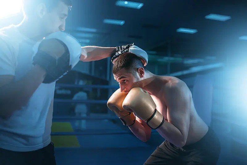 Boxer in gloves exercises head movement with sparring partner