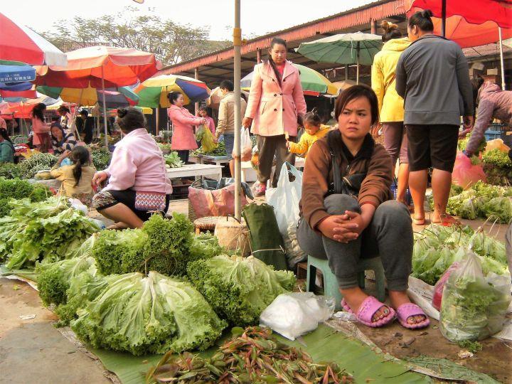 Mujer en puesto de hortalizas en mercado de Laos