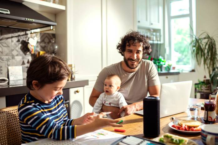 Man with infant and son working with a smart home device on the table.