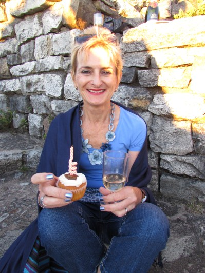 The Birthday Girl with a cupcake and glass of champagne on top of Table Mountain