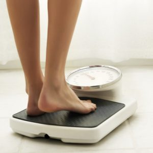 Young woman standing on a bathroom scale