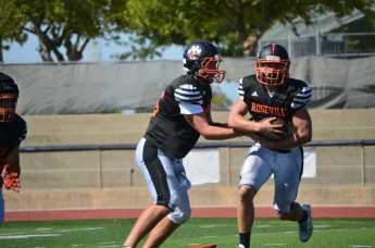 (SAM MAILEY) Senior quarterback Nick Martig works with running back Brendan McMinn last week.