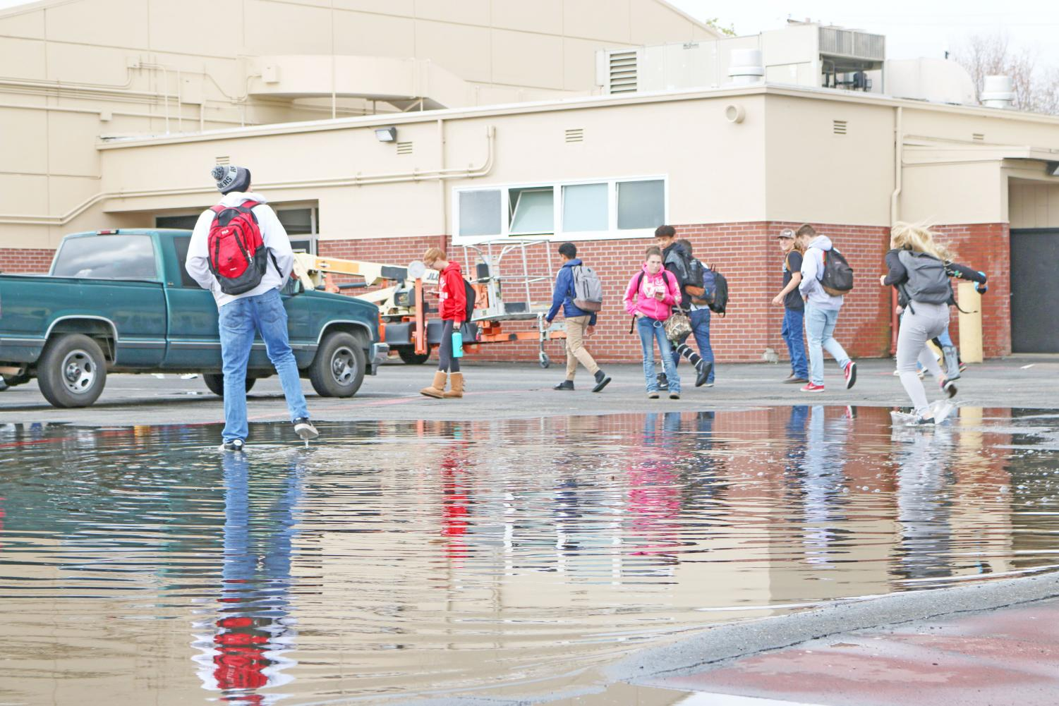 """Students splash in the shallow end of the flooded area in the 900s parking lot last Thursday. The RHS community has given this area the name """"Lake Roseville."""" (SINO OULAD DAOUD/EYE OF THE TIGER)"""
