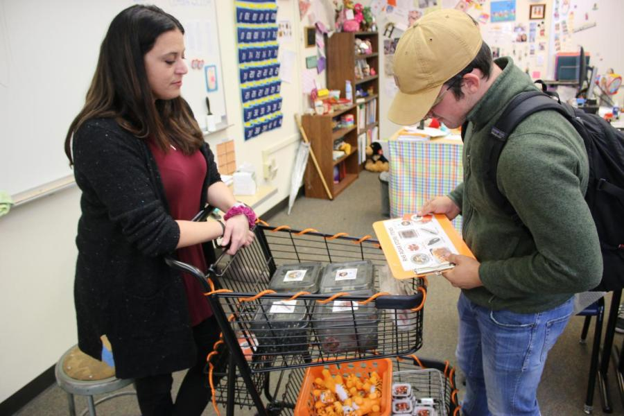 PBIS coordinator Jamie Handling sells a student items at the traveling ROAR store.