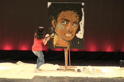 A student paints a portrait at the talent show.