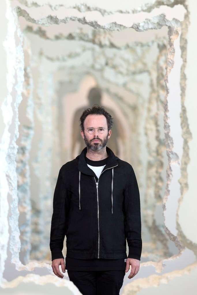 "Daniel Arsham in front of his work ""Wall Excavation"" 2016, Styrofoam joint compound, Dimensions-variable. Commissioned by the SCAD-Museum-of-Art-Savannah. Photo courtesy of-SCAD Photography by John McKinnon"
