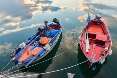 Alfonso Di Vincenzo Two small wooden fishing boats in the port of Corigliano Calabro, Calabria, Southern Italy, under the sky at sunset reflected in the calm waters of the sea. (1) Base d'asta 100 euro