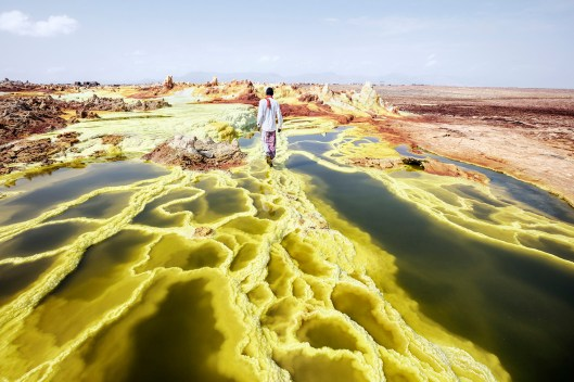 "Dallol, means the ""Hill of the Spirits"" for the Afar people. Is the land of geysers, crystal formations and sulphurous springs. In this picture my guide in Dallol, Alì, walking through the landscape. Alì Arata (Afar ethnic group), 23 years old, lives in Hamed Ela, and for 10 years he has been working as a guide accompanying travelers to Dallol and to the volcano Erta Ela. Dallol is a volcanic explosion crater in the Danakil Depression, Ethiopia. These craters are the lowest known sub-aerial volcanic vents in the world, at over 45 m (150 ft) below sea level. Dallol is also known to be the hottest place on earth. The average daily-maximum_temperatures here could be of 110 °F. Acidic water, salt, sun, wind, impossible and violent rains have found a fertile desert for their art. Numerous hot springs are discharging brine and acidic liquid here. Widespread are small, temporary geysers, which are forming cones of salt. The term Dallol was coined by the Afar people and means dissolution or disintegration, describing a landscape made up of green acid ponds. © Andrea Frazzetta"