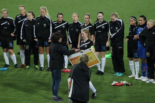 ÖSK Söders lagkapten Sandra Johansson tar emot prischecken.
