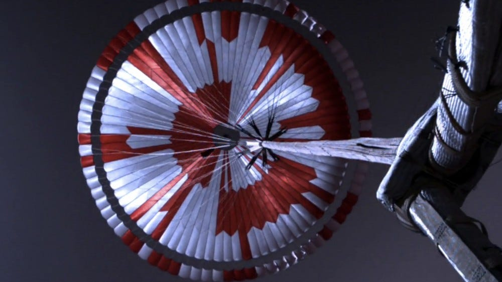 A photo of the red and white Mars rover parachute.