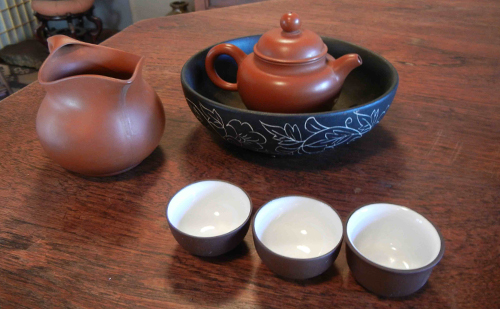 """Kung fu tea set up with """"red clay"""" yi xing teapot, tea boat, ceramic """"tea ocean"""" decanter, and cups."""