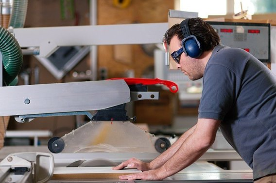 A carpenter is using table saw