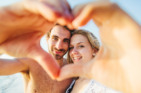 Sunset, sandy beach, a loving couple stops during a walk. A man and a woman are photographed at sunset through a heart made with their hands