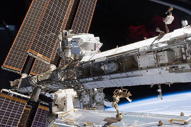 A Estação Espacial Internacional, em órbita da Terra, onde está o detector usado no experimento (no centro, acima)