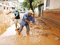 Homens limpam ruas em Mira� após rompimento de barragem de mineradora, por Folha OnLine