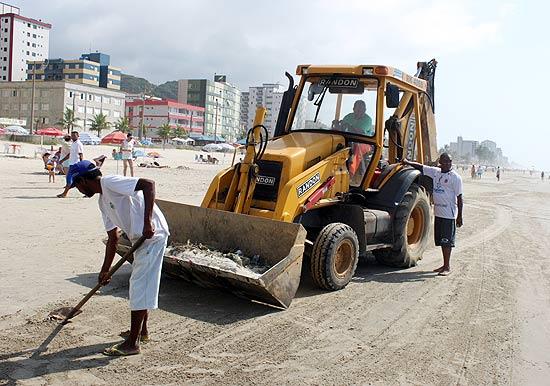 Funcionários da prefeitura trabalham na limpeza de praias de Mongaguá, em SP, após aparição de peixes mortos