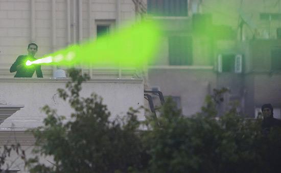 Manifestante usa caneta de laser verde durante protesto no Egito; raio prejudica voos quando apontado para o piloto