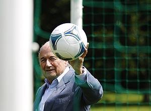 Blatter posa com uma bola na sede da Fifa, na Suíça