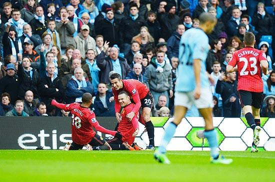 Rooney (ajoelhado no centro) festeja um dos seus gols no clássico ante o City
