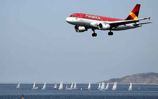 In the forefround an Avianca airliner lands in the Santos Dumont airport (not framed) as sailing boats compete in the International Sailing Regatta held in the Guanabara Bay in Rio de Janeiro, Brazil on August 19, 2015, an event that serves as a test for the Rio 2016 Olympic Games. AFP PHOTO/VANDERLEI ALMEIDA ORG XMIT: VAN971LEGENDA DO JORNALAvião da Avianca pousa no aeroporto de Santos Dumont