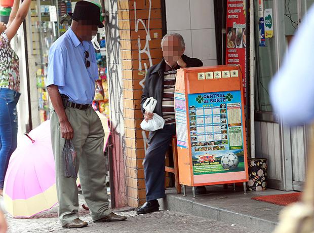 Homem se aproxima de balcão de jogos na avenida São João