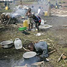 Meninos preparam comida em campo de deslocados; conflito causou fuda de 250 mil