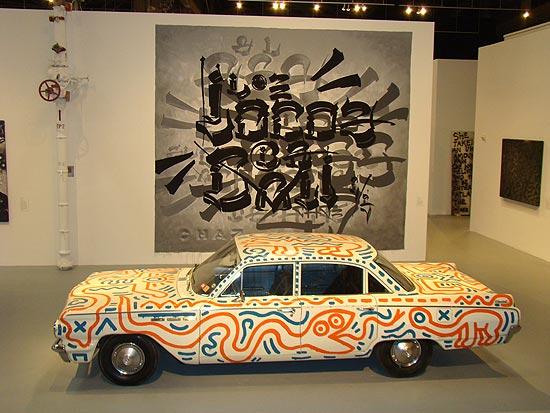 Carro pintado por Keith Haring, em frente à tela de Chaz Bojórquez.