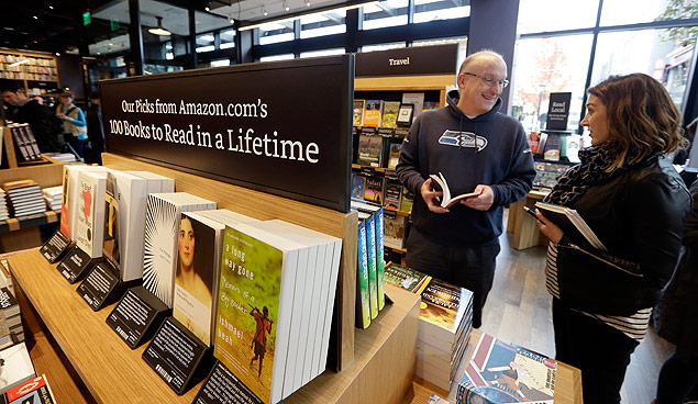 Customer Jeff Edward, left, talks with Amazon employee Sarah Gelman as Edward shops at the opening day for Amazon Books, the first brick-and-mortar retail store for online retail giant Amazon, Tuesday, Nov. 3, 2015, in Seattle. The company says the Seattle store, coming two decades after it began selling books over the Internet, will be a physical extension of its website, combining the benefits of online and traditional book shopping. Prices at the store will be the same as books sold online. (AP Photo/Elaine Thompson) ORG XMIT: WAET106