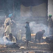 Refugiados cozinham na rua em Kibati, perto de Goma; mais de 1 milhão fugiu dos conflitos