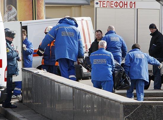 Paramédicos carregam vítima de duplo atentado em metrô de Moscou;  polícia procura três cúmplices de ataque