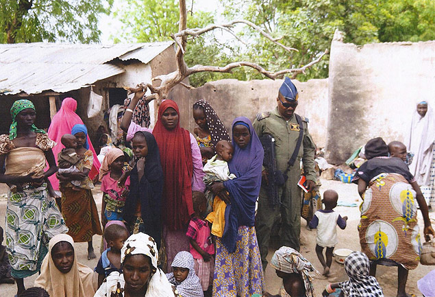 "BEST QUALITY AVAILABLE This handout picture released by the Nigerian army on April 30, 2015 and taken this week in an undisclosed location in the Sambisa Forest, Borno state, purportedly shows a member of the Nigerian Army standing next to a group of women and children rescued in an operation against the Islamist group Boko Haram. Boko Haram hostages were held in atrocious conditions in the group's Sambisa Forest stronghold, Nigeria's military said on April 30 after nearly 500 women and girls were released this week. AFP PHOTO / NIGERIAN ARMY -- RESTRICTED TO EDITORIAL USE - MANDATORY CREDIT "" AFP PHOTO / NIGERIAN ARMY "" - NO MARKETING NO ADVERTISING CAMPAIGNS - DISTRIBUTED AS A SERVICE TO CLIENTS -- ORG XMIT: NIGERIA04"