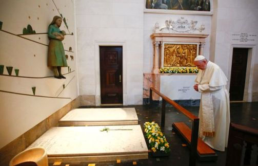 Pope Francis prays in front of the grave of two of the three little sheperds at the Shrine of Our Lady of Fatima in Portugal on May 13, 2017. The two young shepherds, Jacinta and Francisco Marto, who had visions of the Virgin Mary 100 years ago in Fatima, a Portuguese site now a global draw for pilgrims, were declared saints today by Pope Francis. / AFP PHOTO / POOL / TONY GENTILE