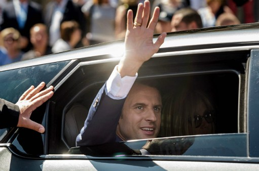 French President Emmanuel Macron (L) waves next to his wife Brigitte Macron as they leave after voting at a polling station during the first round of the French legislative election in Le Touquet, on June 11, 2017. French voters went back to the polls on June 11 for the first round of parliamentary elections that are predicted to give President Emmanuel Macron's centrist party a commanding majority. / AFP PHOTO / POOL / Christope Petit Tesson