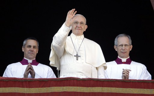 Pope Francis waves to faithful during the Urbi et Orbi (Latin for ' to the city and to the world' ) Christmas' day blessing from the main balcony of St. Peter's Basilica at the Vatican, Monday, Dec. 25, 2017. (AP Photo/Alessandra Tarantino) ORG XMIT: VAT1