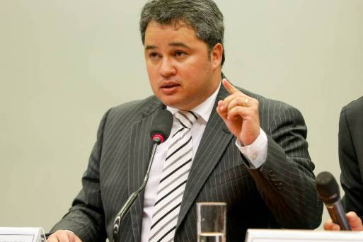 O deputado federal Efraim Filho fala ao microfone. Está de terno cinza, camisa branca e gravata listrada
