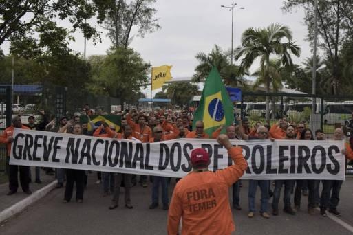 """Petroleiros de uniforme laranja andam em fila segurando faixa que diz """"greve nacional dos petroleiros"""""""