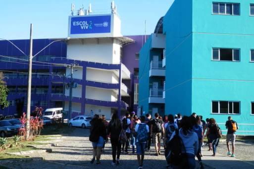 Alunos entrando na escola, um grande prédio azul