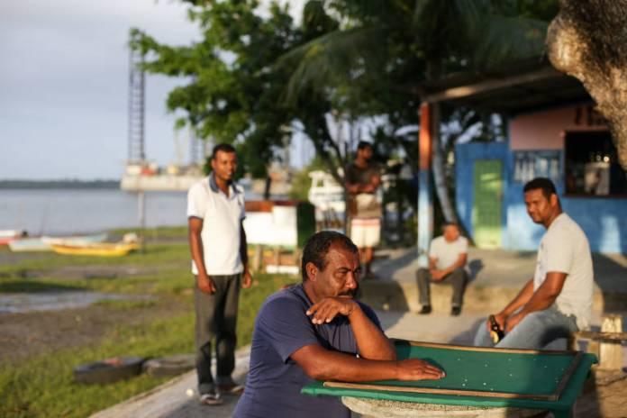 Joilson Borges (sentado, com blusa azul), que ganhava R$ 2.800 mensais no estaleiro e agora voltou a depender da pesca
