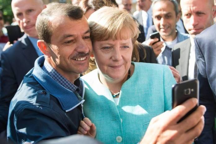 Refugiado faz selfie com a chanceler alemã, Angela Merkel, em Berlim