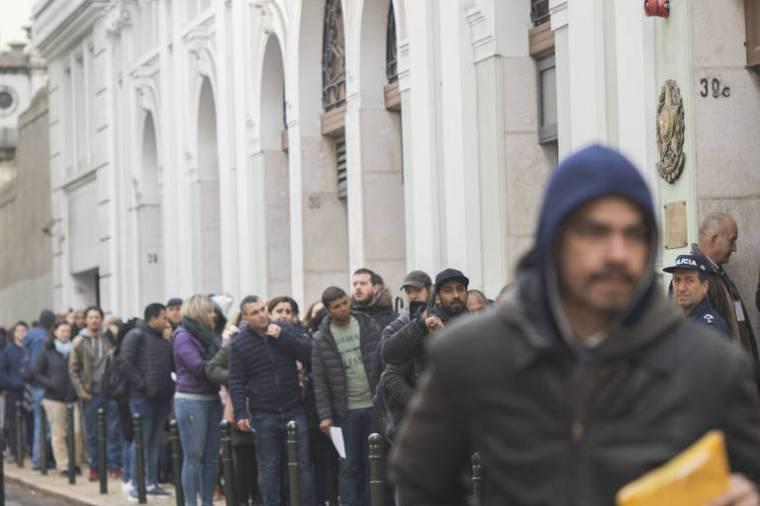 Pessoas vestidas com casacos de inverno fazem fila em calçada de prédio histórico