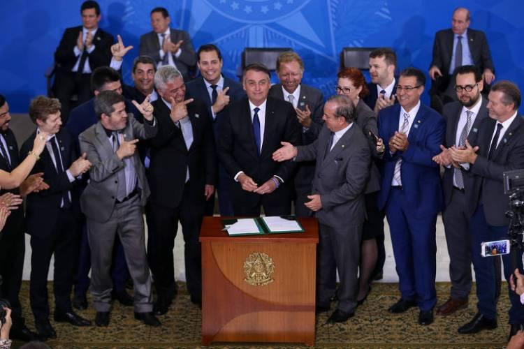 O presidente Jair Bolsonaro, acompanhado de parlamentares favoráveis à projetos de flexibilização do controle de armas, durante assinatura de decreto presidencial