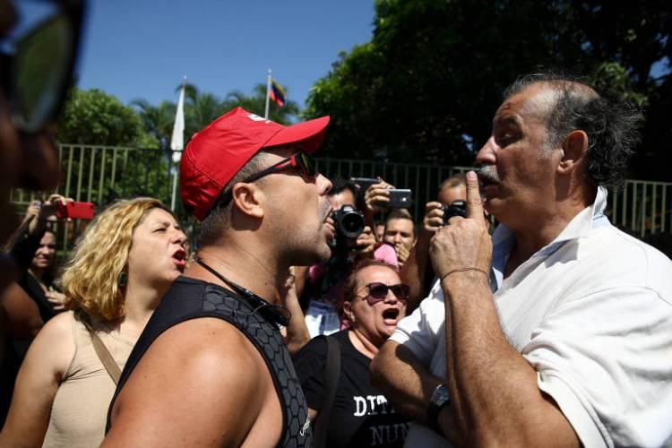 Apoiador de Guaidó (alto, de bigode e camisa branca) discute com militante defensor de Maduro, que usa bone vermelho