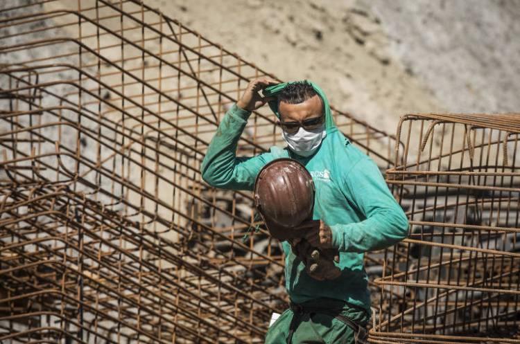 Obras continuam mesmo durante período de quarentena; usando  máscara, operário de construção civil puxa camisa sobre a cabeça durante trabalho em obra de fundação para erguer um edifício residencial na Freguesia do Ó, em São Paulo