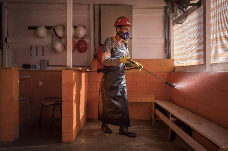 Usando  máscara e luvas de proteção, o operário Martinho Nascimento,42, borrifa uma solução com água, cloro e detergente na entrada para uma obra no bairro Cidade Ademar, em São Paulo; a operação é repetida três vezes ao longo do dia