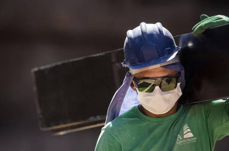 Obras continuam mesmo durante período de quarentena; usando máscara, o operário de construção civil Raimundo José Rosa, carrega material em uma obra de fundação para erguer um prédio residencial de 28 andares na Freguesia do Ó, em São Paulo