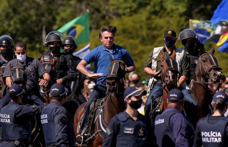 O presidente Jair Bolsonaro cavalga em frente de manifestantes em um cavalo da Polícia Militar durante manifestação em apoio ao governo