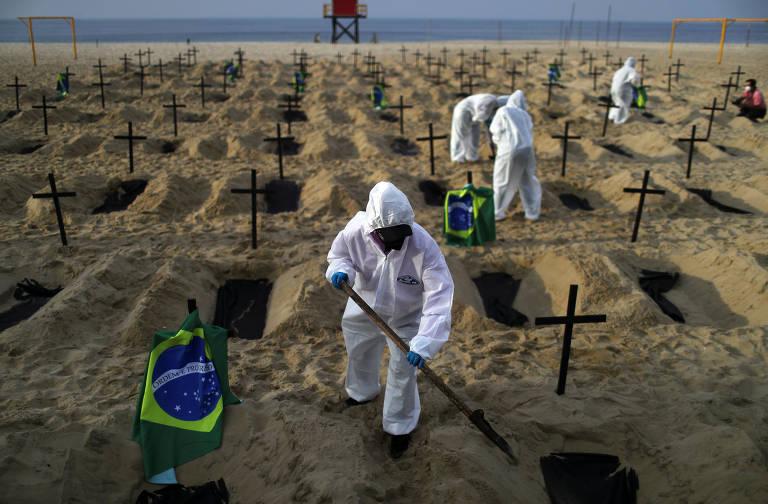 Ativistas da ONG Rio de Paz, entidade de defesa dos direitos humanos, abrem covas na praia de Copacabana para chamar a atenção para as mortes causadas pela Covid-19 no país